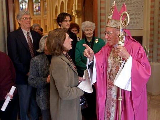 Bishop Harry Flynn speaks with parishioners at St. John's Cathedral on Dec. 15, 2002.
