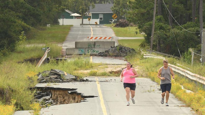 Residents run along Alton Lennon Drive on Wednesday in Boiling Spring Lakes in Brunswick County. Work to rebuild the dams washed out during 2018's Hurricane Florence is not expected to begin until early next year.