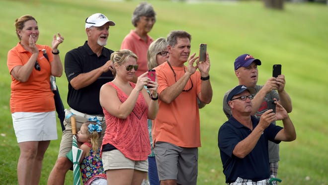 Golf fans watch as Logan Osborne sinks the final putt while capturing the Evansville Courier & Press City Tournament finishing at 4-under par at Evansville Country Club in Evansville Sunday.