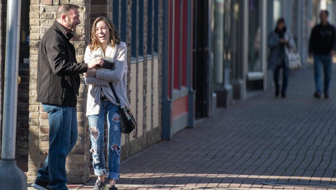 People walk down East Main Street in downtown Richmond on Small Business Saturday, Nov. 25, 2017.