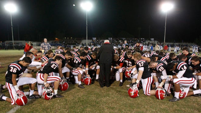 Phoenix Brophy Prep's football team prays with Father Harry Olivier after winning a  game against Chandler High at Phoenix College on Nov. 2, 2012