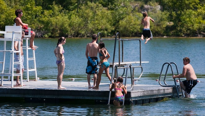 Swimmers line up for a turn on the diving board in Menomonee Park on July 31, 2011. Waukesha County officials are considering major upgrades at the beach house in the park.