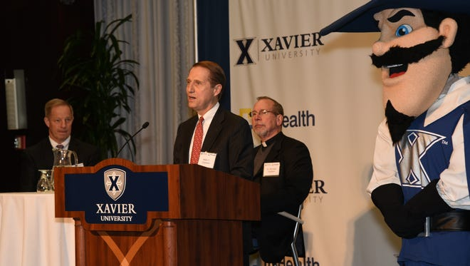 Officials from TriHealth and Xavier University announce the two entities' 10-year collaboration. From left, Dr. Bob Burger, head team physician for Xavier University Athletics, and university President the Rev. Michael J. Graham, listen to Mark Clement, president and chief executive officer of TriHealth, at a news conference at the Cintas Center Thursday. Plus the XU mascot is at right.
