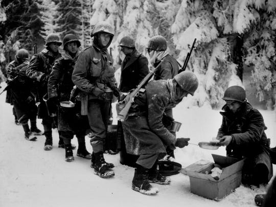 Soldiers in the 347th Infantry Regiment line up for chow during the Battle of the Bulge on their way to La Roche, Belgium in January 1945. Many Battle of the Bulge soldiers went without hot food for weeks during the brutal battle in extremely cold conditions. Courtesy of the National Archives