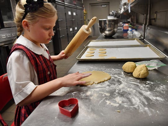 Nikki Goodgion, 9, rolls out cookie dough as she prepares
