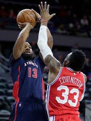 Pistons forward Marcus Morris (13) is pressured by 76ers forward Robert Covington (33) while shooting during the first half of the Pistons' 97-79 loss Sunday at the Palace.
