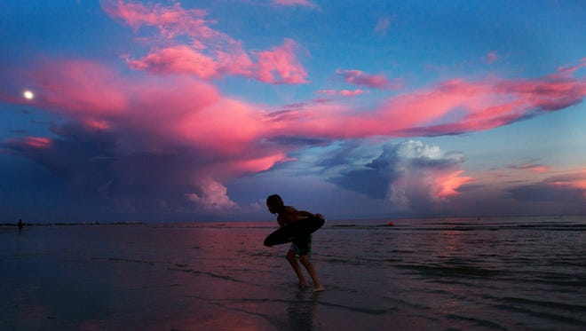Nicholas  Stiens,11, on vacation from Cincinnati takes advantage of a stellar sunset to go skim boarding with his brother and father on August 16, 2016 on Fort Myers Beach.