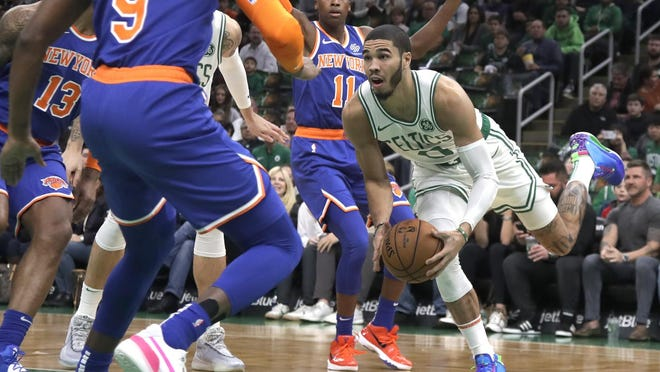 Celtics forward Jayson Tatum tries to navigate through a trio of New York Knick players during a game last November. After much consideration, he said he decided to play in Florida to keep the Black Lives Matter movement front and center with the public.