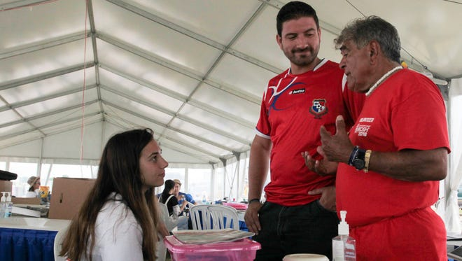 Sofia Benitez, of Argentina, Gustavo Arosemena, of Panama, and El'as Rene Rodriguez, of Puerto Rico, talk inside the International Visitors Tent at AirVenture Wednesday.