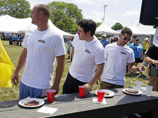 Sheboygan Press Media reporter Jason Smathers listens to the announcer after the Brat Eating Contest at Kiwanis Park in Sheboygan on Saturday.