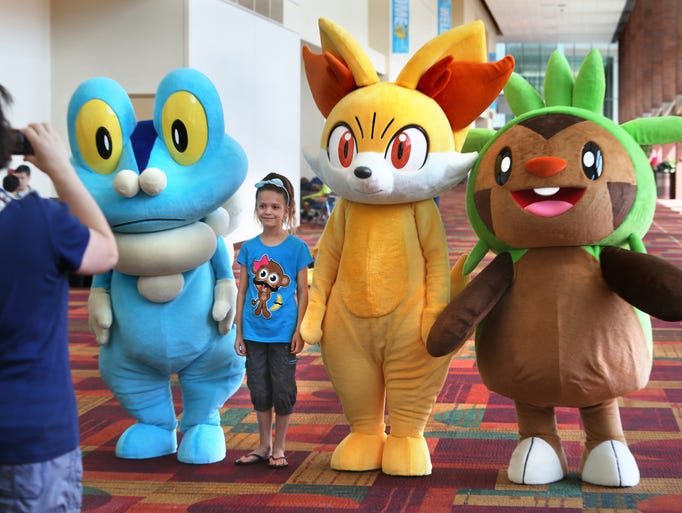 Jennifer Green, Indianapolis, takes a picture of her daughter Mia, 7, with Pokemon characters in a hallway at the Indiana Convention Center in Indianapolis as the 2014 Pokemon U.S. National Championships are held for the fifth consecutive year on Saturday, July 5, 2014.