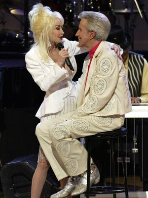 "Dolly Parton sings ""I Will Always Love You"" to Porter Wagoner during the celebration of Wagoner's 50th anniversary with the Grand Ole Opry on May 19, 2007. Parton wrote the song for Wagoner, who was her duet partner from 1967 to 1974."