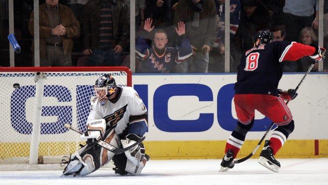 New York Rangers' Marek Malik, right, slips the puck past Washington Capitals goaltender Olie Kolzig in a shootout Nov. 26, 2005, at Madison Square Garden.