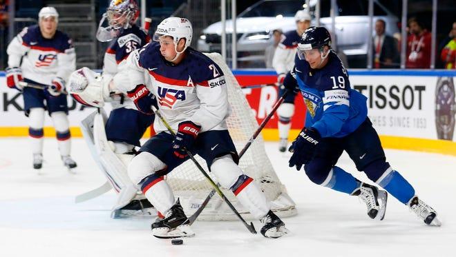 Finland's Veli-Matti Savinainen and USA's Dylan Larkin vie during the IIHF Men's World Championship Ice Hockey  game in Cologne, western Germany, on May 18, 2017.