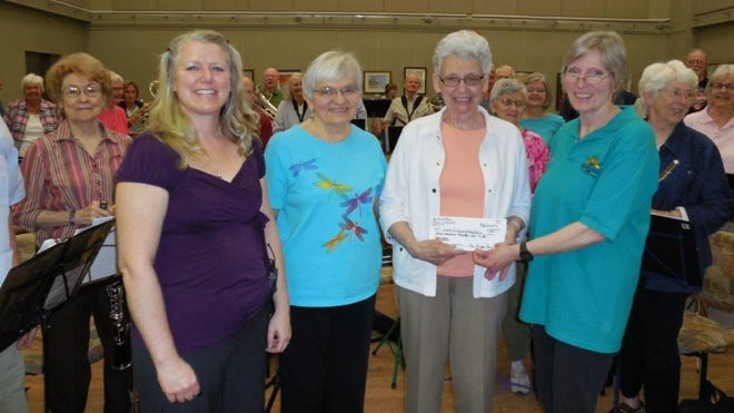 New Horizons Band presents a check to Habitat for Humanity, Women Build 6 in honor of Jean Lloyd-Jones, former band member. Pictured are Erin Wehr, NHB director; Jean Hill, chair of NHB steering committee, Jean Lloyd-Jones and Joyce Marner, band member. They are surrounded by members of the New Horizons Band.