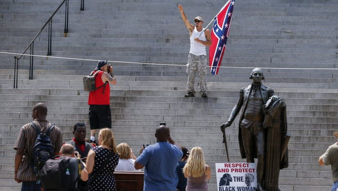 A man displays a Confederate battle flag and gives a Nazi Party salute on the steps of the Statehouse during New Black Panther Party and Ku Klux Klan rallies on the grounds of the South Carolina Capitol in Columbia, South Carolina Saturday.