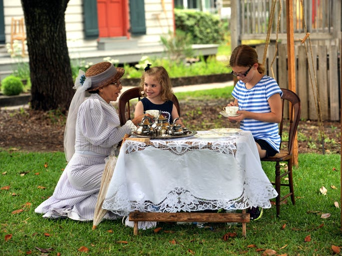 Katya Nossa-Sarasty shows Lydia and Victoria Dooley how to have tea Saturday during the Historic Pensacola Village Open House.