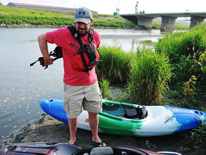 Mitchell Joldersma, of Sioux Falls, who is currently in the process of trying to open a whitewater park on the Big Sioux River, puts a life vest on before launching a kayak in a part of the river near Lien Park, which could be a possible location for a whitewater park, on Thursday, July 17, 2014, in Sioux Falls, S.D.