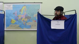A man casts his vote at a polling station as the map of Europe is seen on the wall in Athens, Sunday, Jan. 25, 2015.