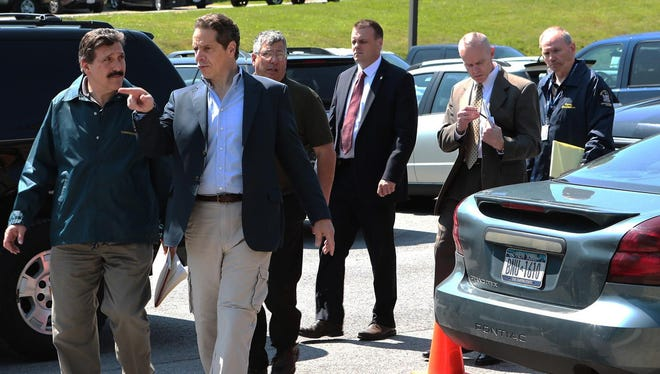 Gov. Andrew Cuomo speaks with Acting State Department of Corrections and Community Supervision Commisioner Anthony Annucci as he arrives for a news conference.