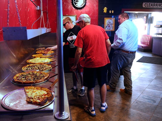 Diners line up to grab slices of pizza from the buffet