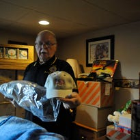 Ron Miller, American Legion Wood County commander, shows off an embroidered cap , one of hundreds of presents he'll give veterans at the Veterans Home in King.
