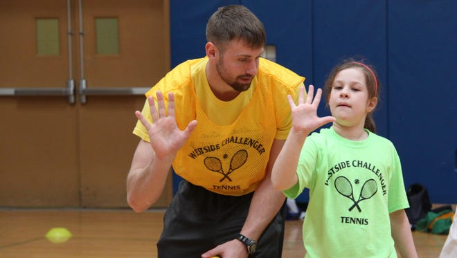 Nick Faulds, a senior at the College at Brockport, works with Aaliyah Stephens, 8.