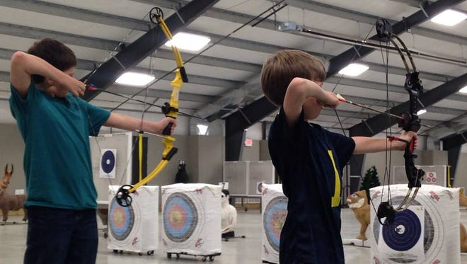 Drew Jamison, left, 12, and Jack Lewandowski, 8, pull back an arrow during their lesson at Full Quiver and More.