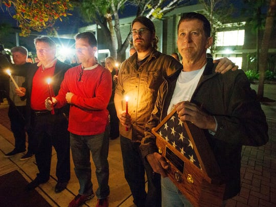 Tim Jardas, right, father of U.S. Marine and Cypress Lake High School graduate Thomas Jardas attends a vigil for his son at Cypress Lake High School in Fort Myers on Thursday. Thomas is one of 12 Marines missing after a helicopter crash off the coast of Hawaii during night training exercises on Jan. 14.