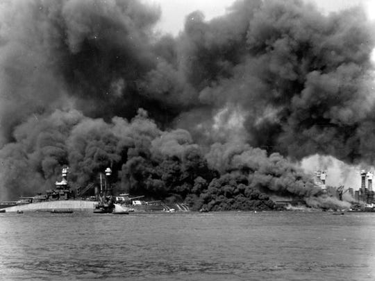 The capsized USS Oklahoma is at left, alongside the USS Maryland. Crewmen on the latter's stern are using fire hoses to try to push burning oil away from their ship. At right, oil fires shroud the sunken USS West Virginia and the USS Tennessee.