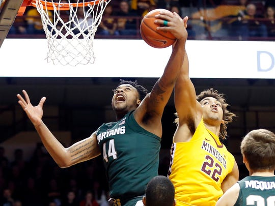 Minnesota's Reggie Lynch, right, tries to knock away a pass to Michigan State's Nick Ward during the first half Tuesday in Minneapolis.