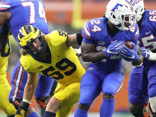 Michigan's Noah Furbush tackles Florida's Mark Thompson