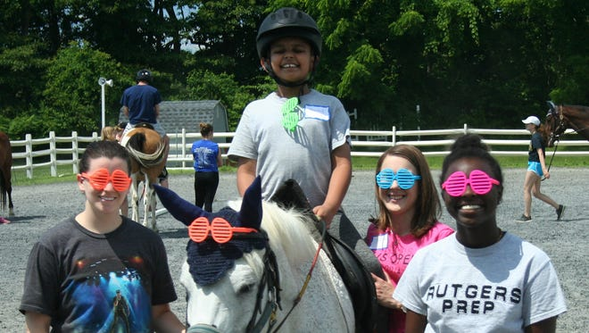 Jainil Patel of Princeton rides with the aid of dedicated volunteer buddies at Mane Stream's Summer Camp for ALL Abilities.The organization is hosting an Open House from 10 a.m. to 3 p.m. Sunday, April 8for the communityto learn about Mane Stream'sprograms and services, including summer day camp, equine assisted therapiesand adaptive riding.