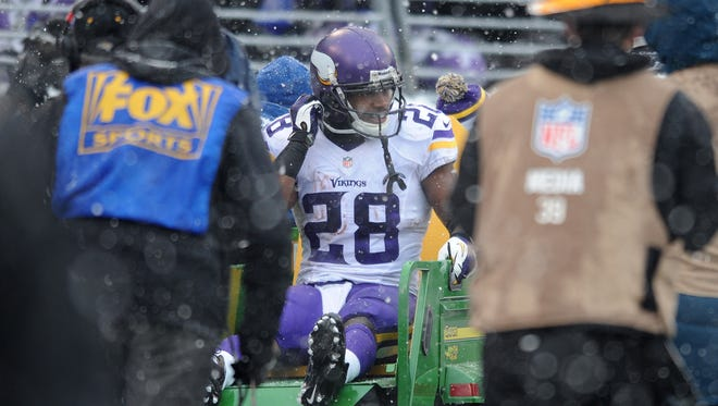 Vikings RB Adrian Peterson is carted off the M&T Bank Stadium field on Sunday.