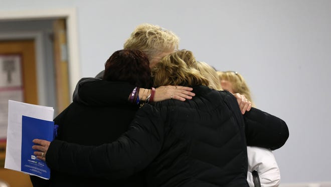 Mothers whose families have been touched by addiction share a hug at the end of a Gates to Recovery session in Gates.
