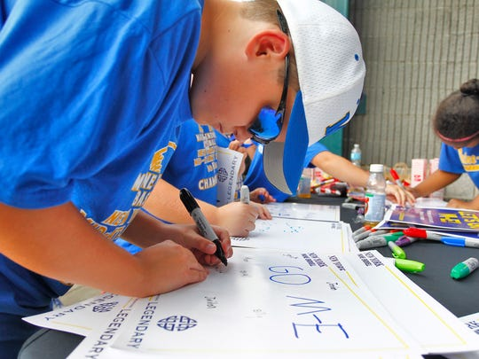 Shane Gorton, 11 of Endwell decorates a poster for the game during an M-E pep rally held at Dick's in Vestal on Thursday, August 18, 2016. 