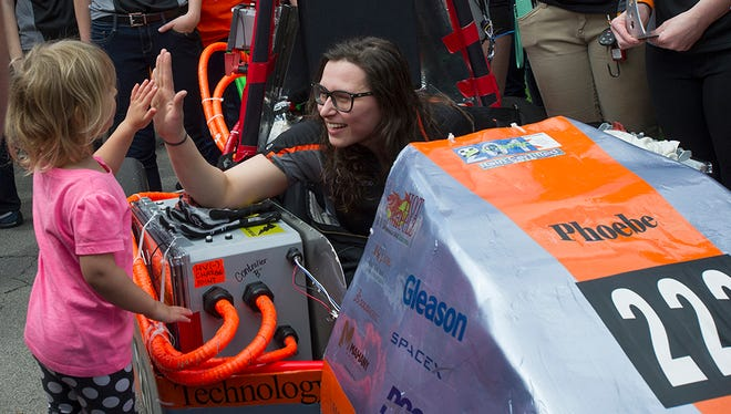 Maura Chmielowiec, chief engineer for the Hot Wheelz team at Rochester Institute of Technology, high-fives a young girl at the 2016 Imagine RIT: Innovation and Creativity Festival.