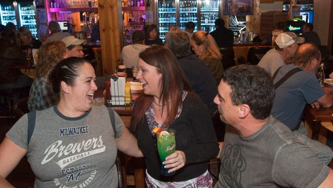Jennine Paoli (center) talks to patrons April and Glen Blok as they enjoy the evening at a past trivia night at Saloon on Calhoun in Brookfield.