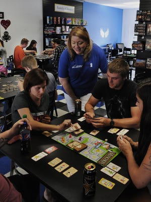 Jeanne Sikoff, owner of Zander's Game House, watches Heather Reed, from left, Jonathan Stribling and Tyler Conner play Munchkin, one of more than 700 board games patrons can play. Sikoff's business is riding the wave of board games' resurgence.