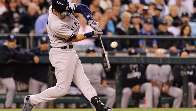 Yankees shortstop Derek Jeter hits a two-run single against the Mariners during the fourth inning at Safeco Field Thursday night.