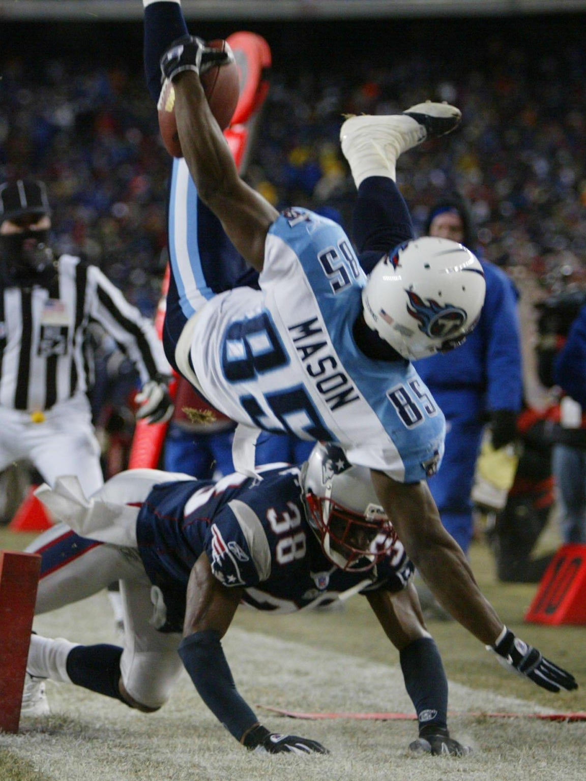 New England Patriots' Tyrone Poole (38) can't stop Tennessee Titans Derrick Mason (85) from scoring a touchdown in the third quarter of their AFC playoff game at Gillette Stadium, Saturday, Jan. 10, 2004, in Foxboro, Mass..