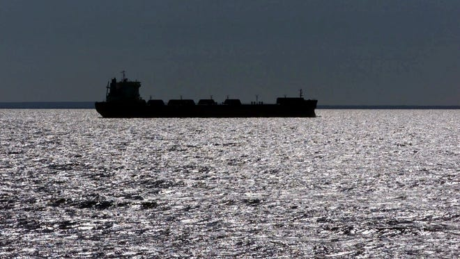 A freighter is silhouetted on Lake Superior in July 199 near Whitefish Point, Mich. A plan gaining support in Congress and backed by the cargo shipping industry would establish a nationwide policy for treating ballast water dumped from cargo ships into U.S. waterways.  Environmental groups say that would open the door to more invasive species like zebra and quagga mussels, which have wreaked havoc from the Great Lakes to the West Coast.
