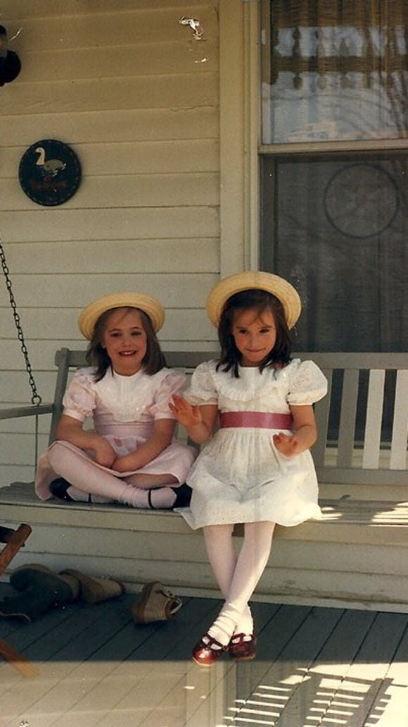 Abbey Doyle and twin sister Sarah Spurgeon sitting on the back porch of their childhood home on Easter morning.