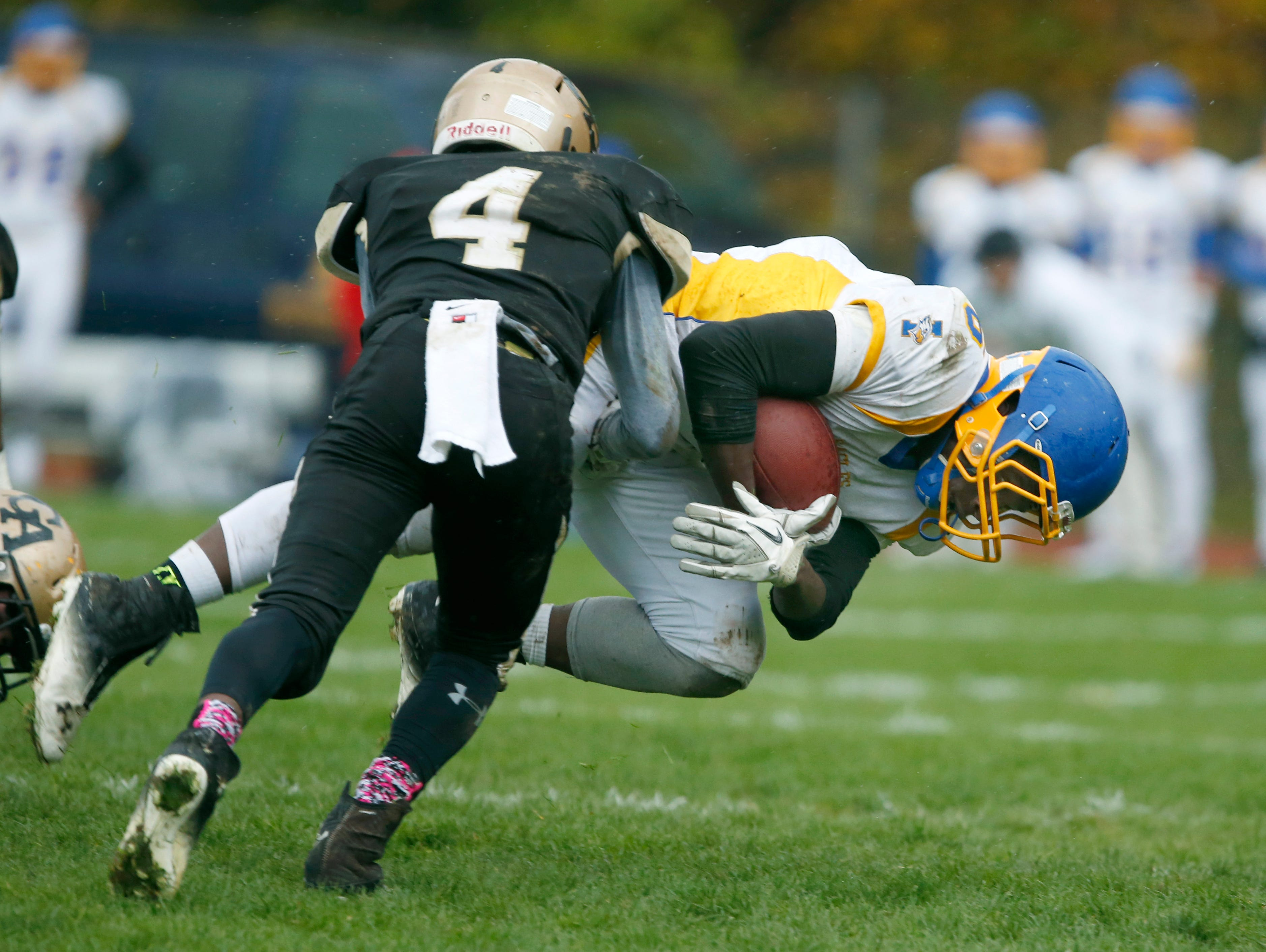 Irondequoit's Shawn Jones is tackled by Greece Athena's Kenny Speed in the second quarter at Greece Athena High School.