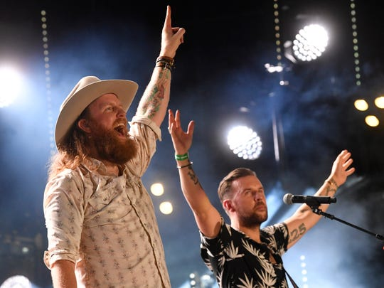 The Brothers Osborne gesture to the crowd at the 2018