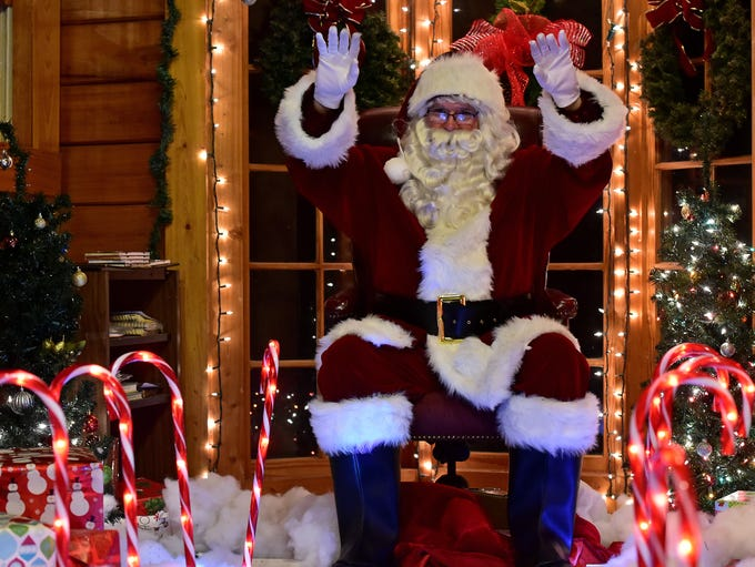 Santa Claus waves to visitors during the Deck the Trails