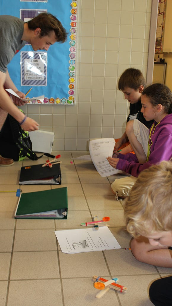 Alec Vent helps Casey, Sarah, Kaitlin and Chase prepare their catapults for launching (J. Baier)
