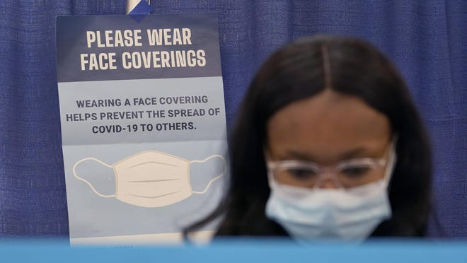 A Chicago resident wears a protective mask Thursday, Oct. 15, 2020, as she participates in early voting at the Dr. Martin Luther King, Jr. Center in Chicago.
