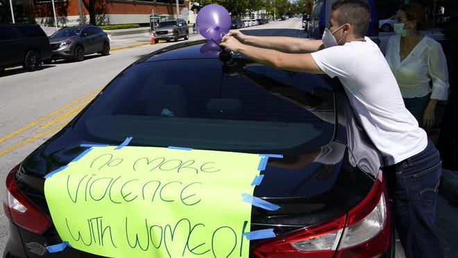 Juan Torres ties a balloon on a vehicle in preparation for a car caravan organized by Survivor's Pathway in recognition of National Domestic Violence Awareness Month beginning in October, Wednesday, Sept. 30, 2020, in Miami. Mental health advocates say the COVID-19 pandemic has caused additional issues in intimate partner violence.