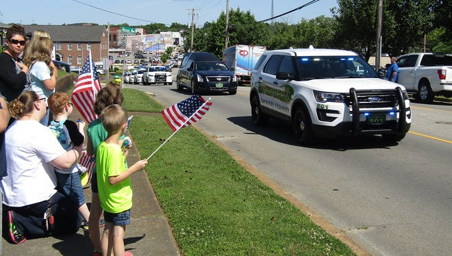 Many people paused Monday morning along College Street in downtown Dickson to pay their respects as the body of Sgt. Daniel Baker was transported from Taylor Funeral Home to First Baptist Church Dickson.